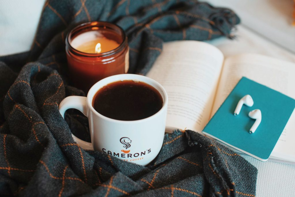 Scene of Cameron's Coffee white 10oz. mug surrounded by a plaid blanket, a candle and an open book.