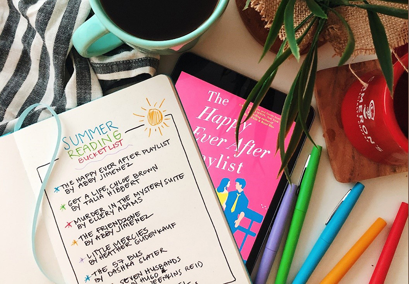 Variety of markers, coffee mug and summer reading list on table